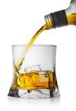 倾吐从瓶的威士忌酒入与冰的一块玻璃 免版税库存图片