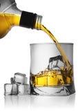 倾吐从瓶的威士忌酒入与冰的一块玻璃 图库摄影