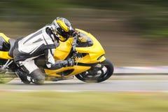 倾斜入一个快速的角落的摩托车在轨道 免版税库存照片