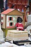 倾斜反对一个木玩具房子的黑玩偶 免版税库存照片