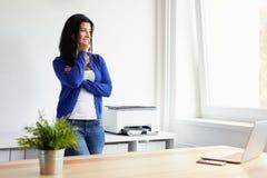 倾斜反对一个架子的妇女在办公室 免版税库存照片