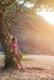 倾斜反对与绿色密林的树的比基尼泳装的可爱的亭亭玉立的女性游人在看天空的背景中明亮 库存图片