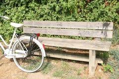 倾斜反对公园长椅的自行车 免版税库存照片