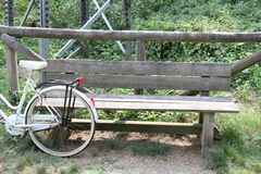 倾斜反对公园长椅的自行车 免版税库存图片