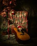 倾斜反对古色古香的椅子的葡萄酒声学吉他 免版税库存图片
