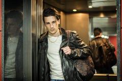 倾斜反对在电梯或推力的镜子的英俊的年轻人 库存图片