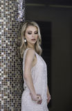 倾斜反对柱子的软的金礼服的性感的都市妇女 免版税库存图片