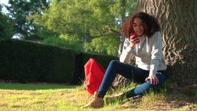 倾斜反对树的混合的族种非裔美国人的女孩少年使用社会媒介的一台手机照相机 影视素材