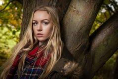 倾斜反对树的青少年的画象 库存照片