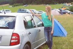倾斜反对汽车的少妇在宿营地在节日 库存照片