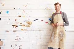 倾斜反对油漆的男性艺术家画象盖了墙壁 免版税库存照片