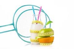 倾斜反对瓶的两副蓝色羽毛球拍蛋白质饮料和一半苹果和桔子包裹与一把黄色卷尺 库存图片