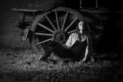 倾斜反对老无盖货车的美丽的农场女孩 免版税库存图片