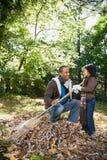 倾斜叶子的父亲和女儿 免版税库存照片