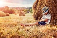 倾斜和睡觉反对干草堆的男孩在日落 库存照片