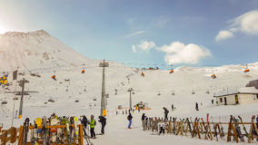 倾斜和滑雪电缆车的未认出的滑雪者 库存图片