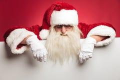 倾斜在一个大空白的委员会的圣诞老人 免版税库存图片