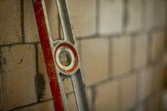 倾斜在一个模糊的砖墙的水平仪 库存照片