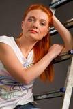 倾斜在一个灰色背景的一架梯子的新红发女孩 图库摄影