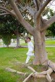 倾斜在一棵大树的年轻人第一个圣餐男孩 免版税图库摄影
