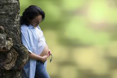 倾斜在一棵异常的树和看她怀孕的腹部的年轻美丽的长发浅黑肤色的男人 免版税图库摄影