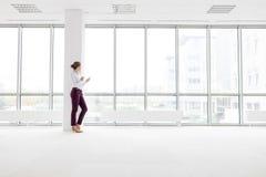 倾斜在专栏的年轻女实业家在新的空的办公室 免版税库存图片