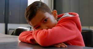 倾斜在书桌的亚裔男小学生正面图在教室在学校4k 股票视频