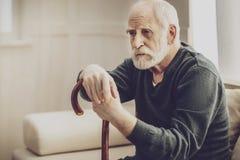 倾斜在他的拐棍的年迈的有胡子的人 免版税库存图片