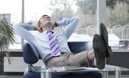 倾斜在他的椅子的年轻商人 免版税图库摄影