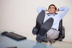 倾斜在他的椅子的微笑的生意人 免版税图库摄影