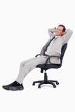 倾斜在他的椅子的生意人侧视图 库存图片
