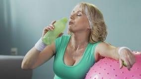 倾斜在健身球,在锻炼,水合作用以后的饮用水的资深妇女 股票视频