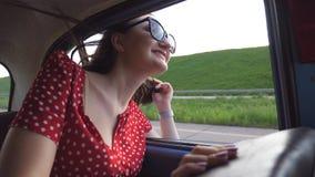 倾斜在减速火箭的车窗外面和享受旅行的太阳镜的愉快的女孩 看窗口移动的少妇老 股票录像