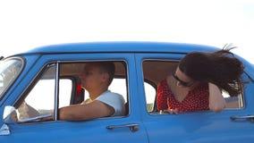 倾斜在减速火箭的车窗外面和享受旅行的太阳镜的愉快的女孩 看窗口移动的少妇老 影视素材
