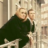 倾斜在城市街道的扶手栏杆的愉快的年轻夫妇 免版税库存照片