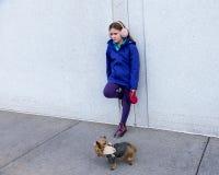 倾斜在墙壁的孤独小女孩,当拿着在皮带时的微小的约克夏狗狗 免版税库存照片