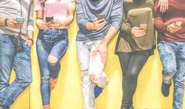 倾斜在墙壁的小组年轻朋友使用手机-连接在人脉的多种族人民用智能手机 免版税库存照片
