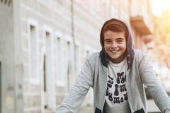 倾斜在墙壁的微笑的年轻男孩 库存照片