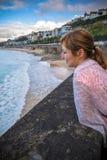 倾斜在墙壁的愉快的微笑的美丽的年轻红发妇女画象,观察波浪和冲浪者岸的 免版税库存图片
