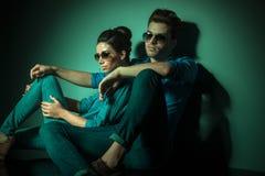 倾斜在墙壁的时尚夫妇 免版税图库摄影