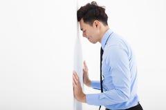 倾斜在墙壁的沮丧的年轻商人在办公室 免版税库存照片