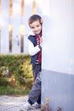 倾斜在墙壁的男孩,微笑 图库摄影