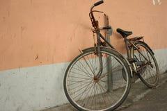 倾斜在墙壁的自行车 库存图片