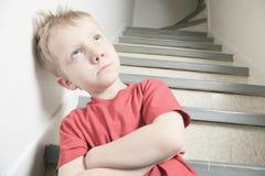 倾斜在墙壁的被忽略的孤独的孩子 免版税库存图片