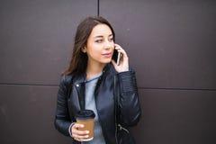 倾斜在墙壁,谈话在巧妙的电话和拿着在papercup的美丽的学生女孩外带的咖啡,听她的interlocu 免版税图库摄影
