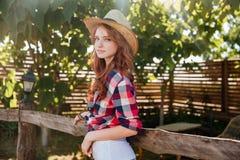 倾斜在大农场篱芭的帽子的逗人喜爱的微笑的红头发人女牛仔 库存图片