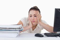 倾斜在她的书桌的哀伤的女实业家 免版税库存照片