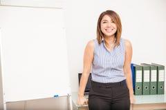倾斜在她的书桌的愉快的老师 免版税库存图片