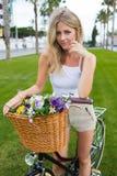倾斜在她的有夏天篮子的经典自行车的微笑的女性骑自行车者开花 免版税图库摄影