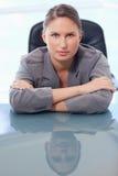 倾斜在她的服务台的一名严重的女实业家的纵向 免版税库存照片